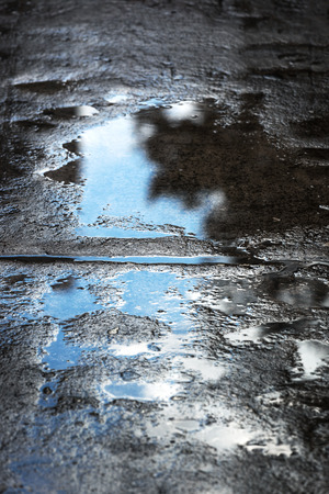 rain puddles on the pavement in the city photo