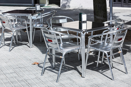 tables and chairs in a cafe on the street photo