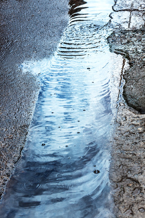 rain stream on the pavement in the city photo