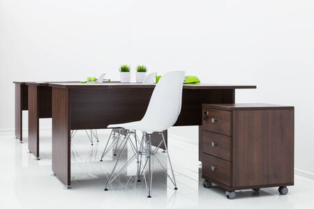 office cabinet: wooden tables and white plastic chairs in the office