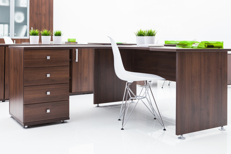desk, chair and bookcase on a white wall