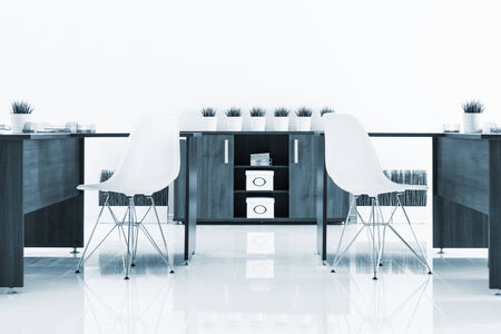 muebles de oficina: escritorios y sillas de plástico con la reflexión en la pared blanca
