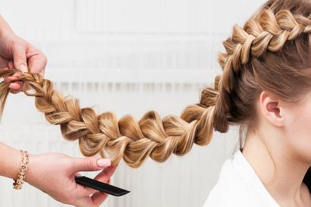 femme blonde: armure tresse fille dans un salon de coiffure Banque d'images