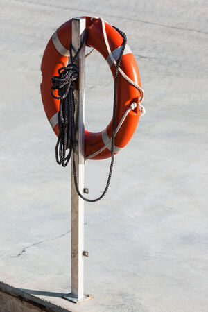 life preserver and rope on a white column photo