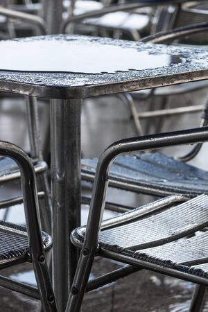 torrential: rain puddle on the table in a cafe