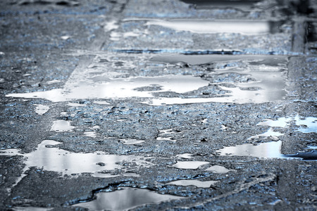 rain puddles on a pavement in the city