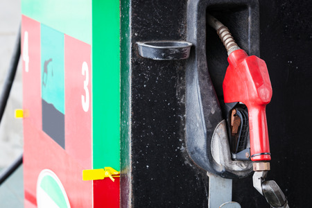 dispense: red refueling hose at petrol gas station