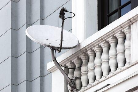 satellite dish: antena parabólica en el balcón de la casa