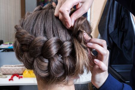 weaving braids woman in a hairdressing salon Stock Photo