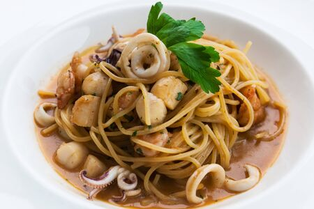 quid: white plate with pasta and seafood