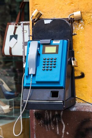 operated: old pay telephone on a city street