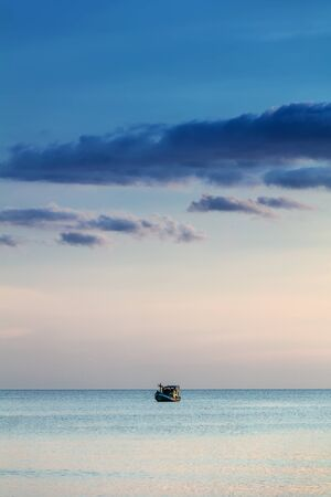 ocean fishing: fishing boat in the ocean at sunset Stock Photo