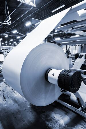 unwinding: unwinding a roll of paper in a modern printing house Stock Photo