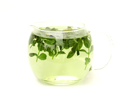 herbal tea in a glass jug on white background photo