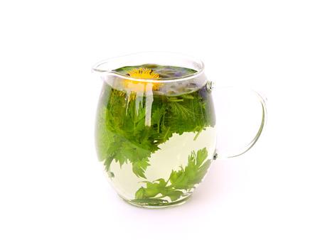 medicina natural: té de hierbas en una jarra de cristal en el fondo blanco