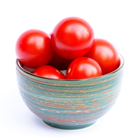 tomatoes in a bowl on a white background