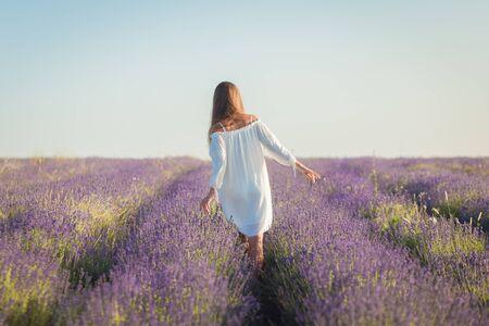 Hermosa mujer joven con un vestido blanco camina en el campo de lavanda