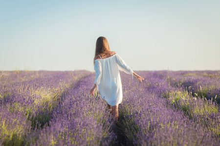 Schöne junge Frau in einem weißen Kleid geht in das Lavendelfeld
