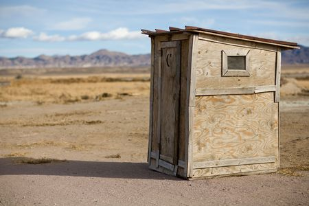 Old wooden outhouse on a remote highway in Nevada with mountains and blue sky with clouds in the background and scrub brush all around.  A moon and star are cut out of the door for light.