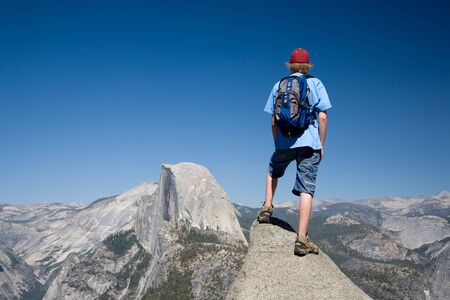 Teenaged boy wearing a blue backpack, red hat, blue shirt and jean shorts standing on a rock point with a view of Half Dome in the distance. Stock Photo