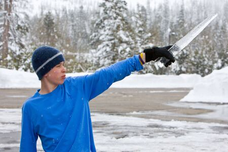 Teenaged boy wearing blue shirt and blue sweater cap and black glove with icicle held like a sword or saber