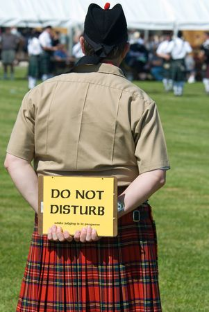 Judge at the Scottish games parade competition, wearing a kilt and holding a sign behind his back that reads,