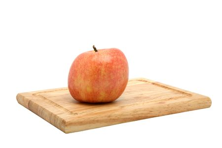 Characteristically lop-sided York apple sitting on a wooden cutting board isolated against a white background.