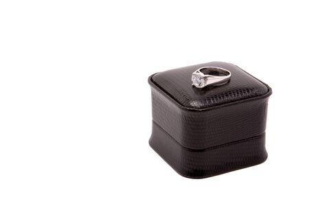 Large diamond encagement ring set in white gold, sitting on top of black box, isolated on white background. Stock Photo