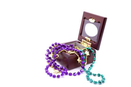 Three strands of Mardi Gras beads in a small wooden jewelry box, isolated against white background. Stock Photo