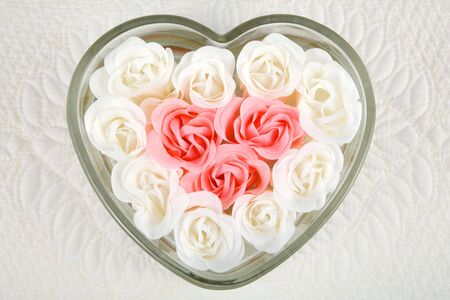 Close up of beautiful pink and ivory roses fill heart-shaped dish against a quilted background. Stock Photo