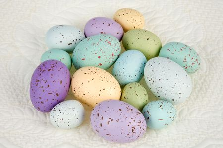 Variety of colored eggs of different sizes, loose against a quilted background.  Room for copy.