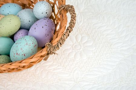 Variety of colored eggs in a basket against a quilted background.  Room for copy.