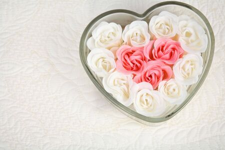Close up of beautiful pink and ivory roses filling heart-shaped dish in upper right corner against a quilted background.  Room for copy. Stock Photo