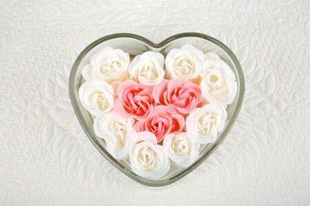 Close up of beautiful pink and ivory roses filling heart-shaped dish against a quilted background with area for copy.