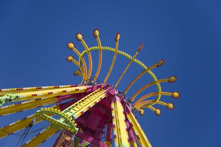 Top of spinning carnival ride against bold blue sky.  Suggests  fun at a summer carnival or fair. Stock Photo