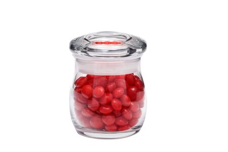 Many pieces of red cinnamon candy in a small jar isolated on a white background great for use alone or in composites. Reklamní fotografie