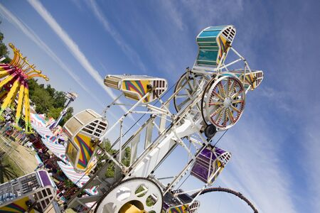 Spinning carnival ride with buckets upsidedown against blue sky.
