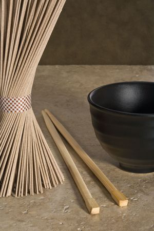 Uncooked buckwheat noodles with chopsticks and tea cup in monochromatic color scheme.