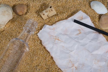 Bottle and cork on sand with sea shells along with paper and charcoal for writing message.