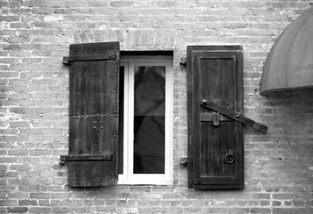 Window with wooden shutters in old brick building.  Image in black and white.