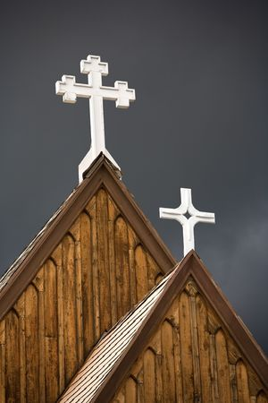 Two white crosses adorn the crest of old wooden church. Stock Photo