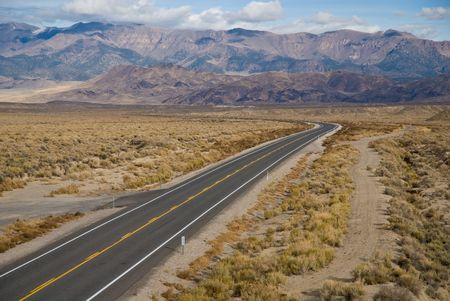 A lonely stretch of deserted desert highway with parallel dirt road, extended into the distance.  Highway 50, Nevada.