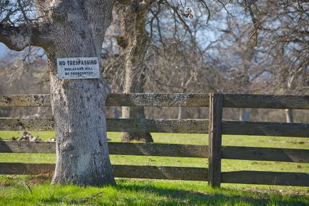 No tresspassing sign on tree by ranch fence.