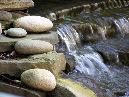 Nahaufnahme der Steingarten mit sanften Wasserfall im Hintergrund.
