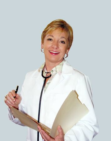 Friendly woman healthcare provider with pen and chart.  Wearing white coat and stethoscope. Stock Photo
