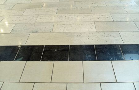 Shining ceramic tile floor with black tile center.