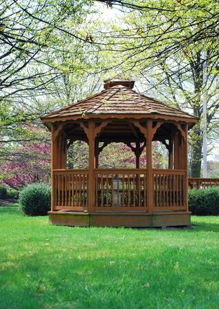 Side view of old fashion gazebo in park with spring cherry blossom in background.