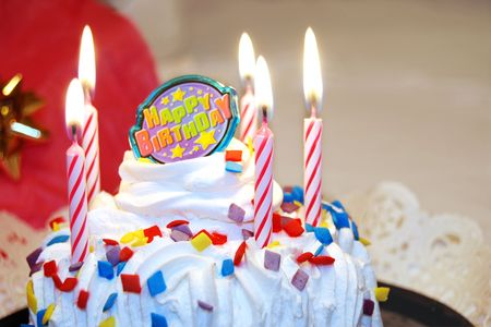Birthday cake decorated with lit candles and colorful sprinkles.