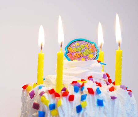 Decorated birthday cake with lit candles and candy sprinkles. Note: Focus on right side.
