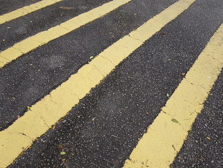 markings: Full frame yellow stripes road markings on black tar road. Stock Photo